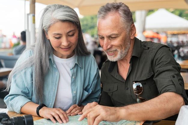 Couple de personnes âgées à plan moyen avec carte