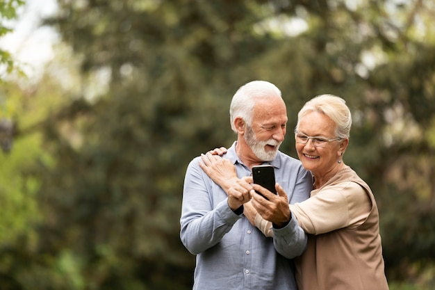 Couple de personnes âgées plan moyen prenant selfie