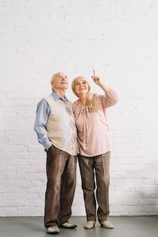 Couple de personnes âgées pointant vers le haut