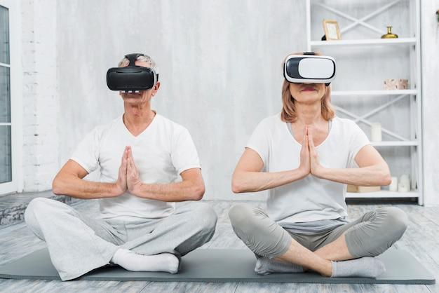 Couple de personnes âgées portant le casque de réalité virtuelle assis sur un tapis avec le geste des mains en prière
