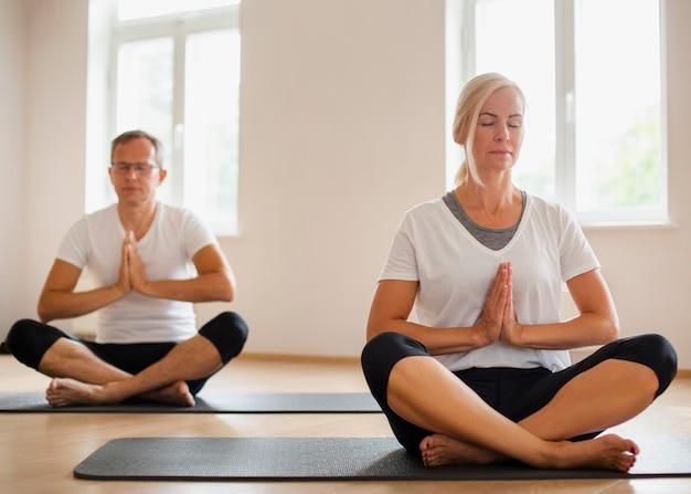 Couple de personnes âgées pratiquant le yoga ensemble