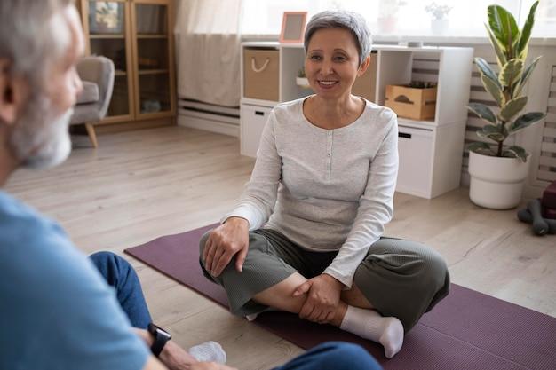 Couple de personnes âgées pratiquant le yoga à la maison