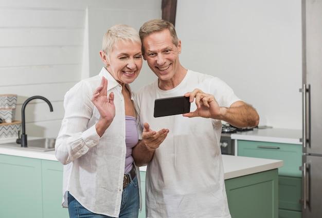 Couple de personnes âgées prenant un selfie dans la cuisine