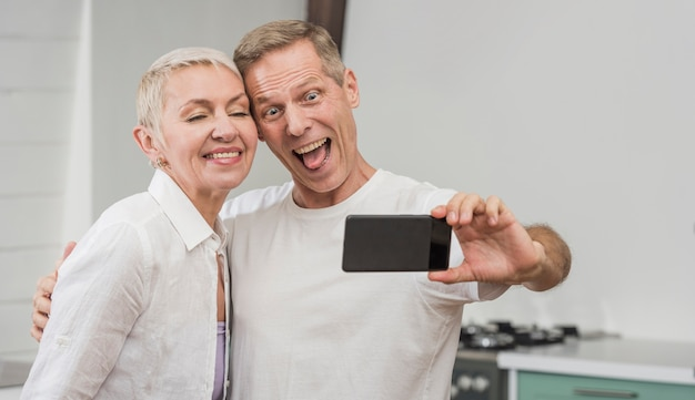 Couple de personnes âgées prenant un selfie à l'intérieur
