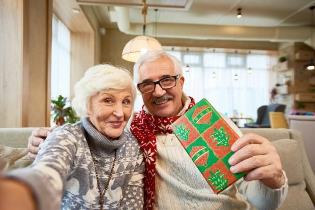 Couple de personnes âgées prenant selfie à noël