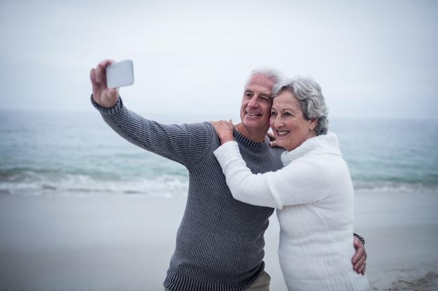 Couple de personnes âgées prenant un selfie sur la plage