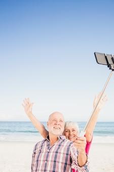 Couple de personnes âgées prenant selfie avec smartphone