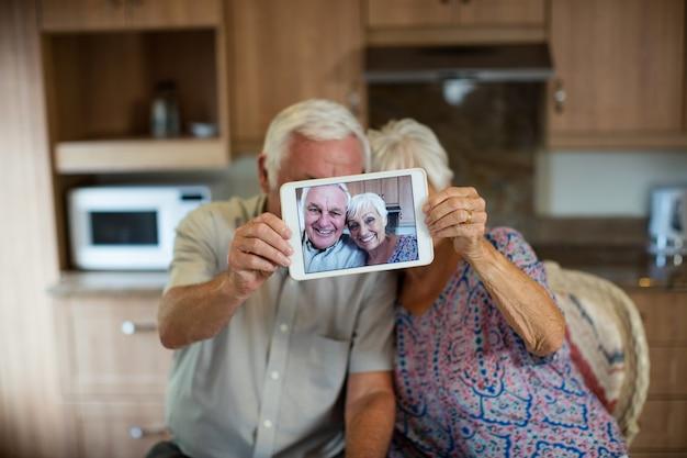 Couple de personnes âgées prenant selfie de tablette numérique dans la cuisine à la maison