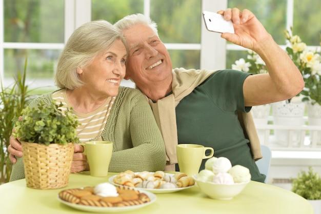 Couple de personnes âgées prenant selfie avec téléphone à la maison