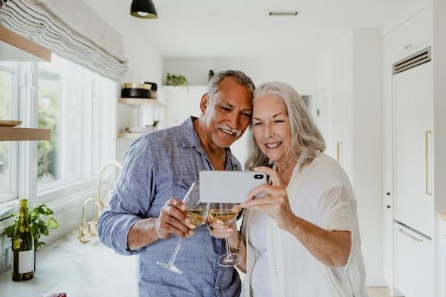 Couple de personnes âgées prenant un selfie tout en buvant un vin
