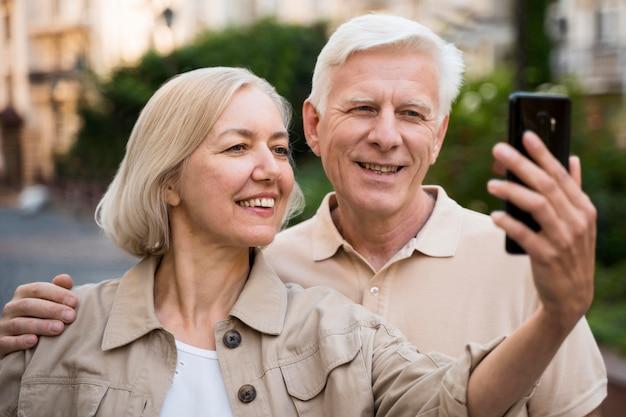 Couple de personnes âgées prenant un selfie en ville
