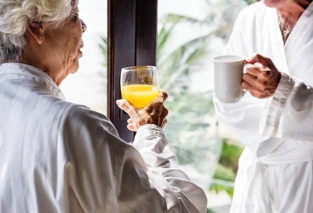 Couple de personnes âgées prenant son petit déjeuner dans une chambre d'hôtel