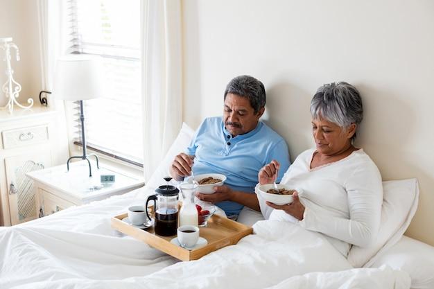 Couple de personnes âgées prenant son petit déjeuner dans la chambre