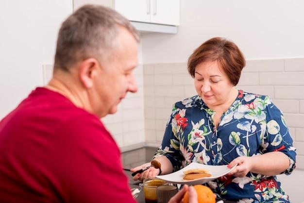 Couple de personnes âgées préparant une crêpe