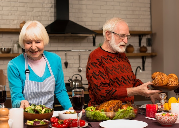 Couple de personnes âgées préparant le repas de thanksgiving
