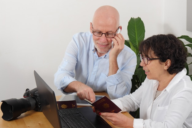 Couple de personnes âgées préparant un voyage de vacances avec passeport