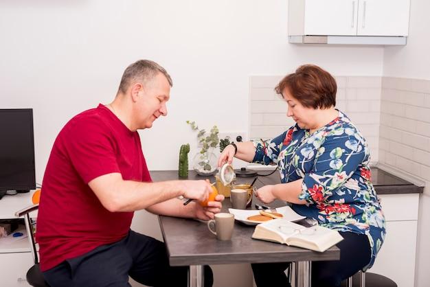 Couple de personnes âgées prépare le petit déjeuner