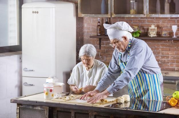 Couple de personnes âgées préparer des pâtisseries dans la cuisine à la maison. l'homme porte une toque.