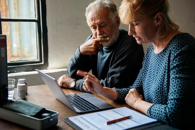 Couple de personnes âgées recherchant des informations en ligne