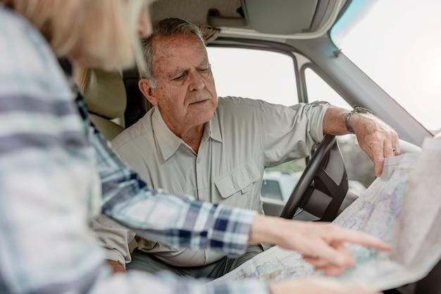 Couple de personnes âgées à la recherche d'une direction sur une carte