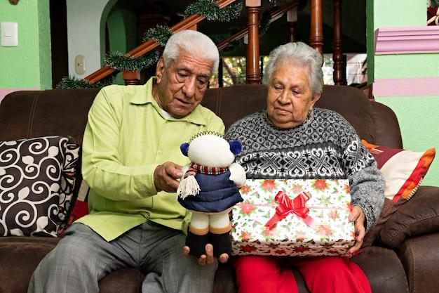 Un couple de personnes âgées regardant un bonhomme de neige et un cadeau assis dans un canapé à noël