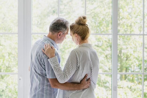 Couple de personnes âgées regardant ensemble par la fenêtre