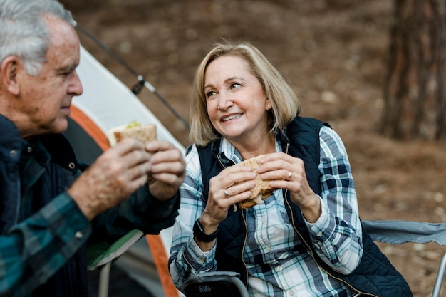 Couple de personnes âgées romantique pique-niquant au camping