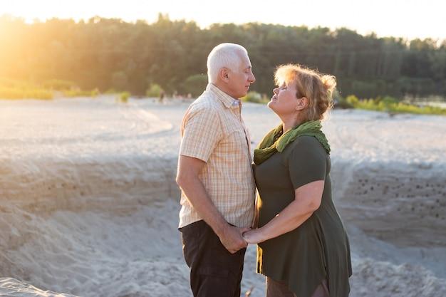 Couple de personnes âgées s'amusant ensemble dans le parc en été.