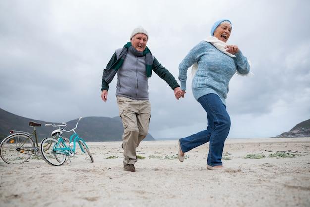 Couple de personnes âgées s'amuser ensemble à la plage
