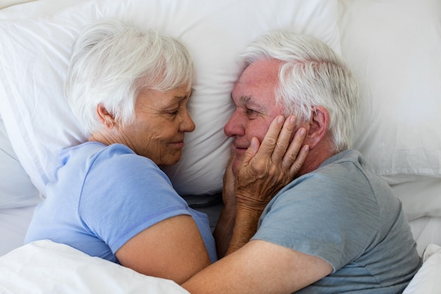 Couple de personnes âgées s'embrassant dans la chambre à la maison