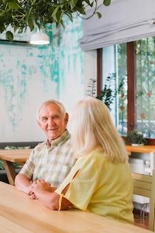 Couple de personnes âgées satisfait assis dans un café et tenant par la main