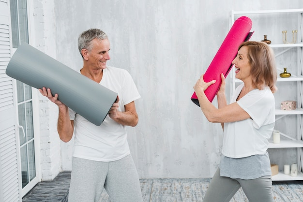 Couple de personnes âgées se battre avec tapis de yoga roulés à la maison