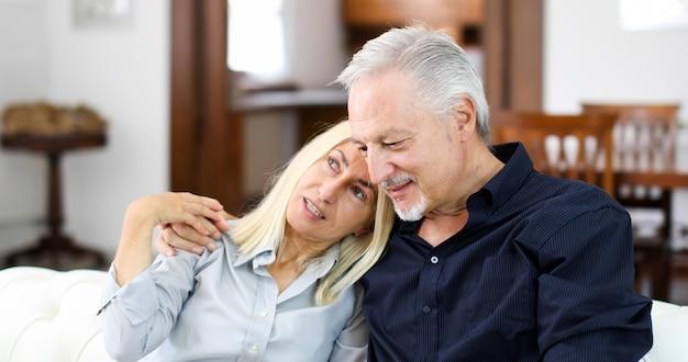 Couple de personnes âgées se détendre sur un canapé et parler ensemble