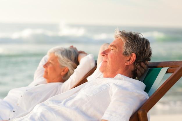 Couple de personnes âgées se détendre dans leurs chaises longues