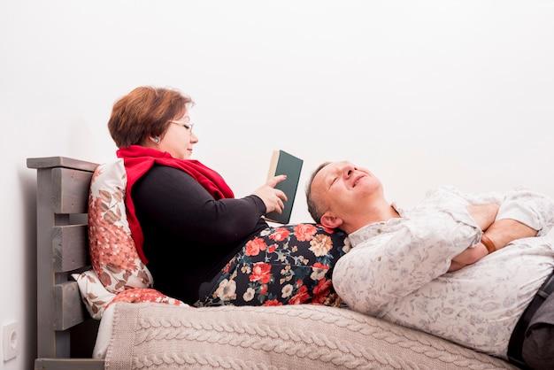 Couple de personnes âgées se détendre sur le lit