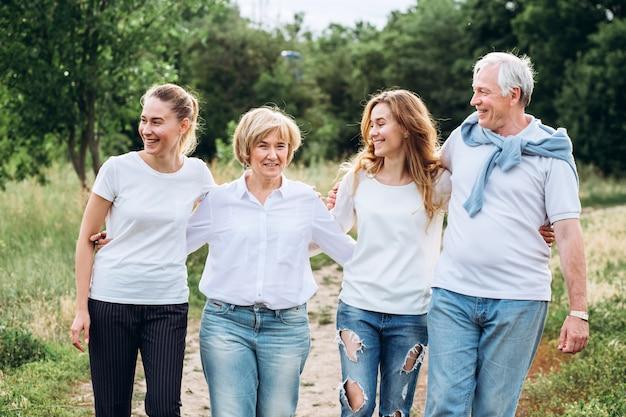 Un couple de personnes âgées se promène avec des filles adultes dans la nature. couple senior se promène dans les bois. une famille en t-shirts blancs et jeans marche dans le parc. famille heureuse. la famille communique à l'extérieur