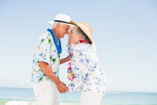 Couple de personnes âgées se regardant sur la plage