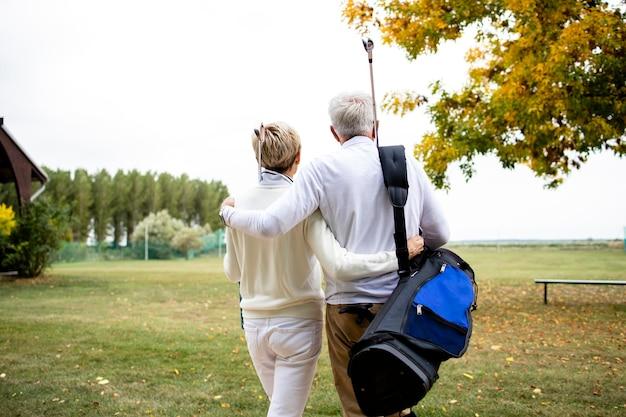 Couple de personnes âgées se tenant ensemble et profitant de loisirs à la retraite en jouant au golf.