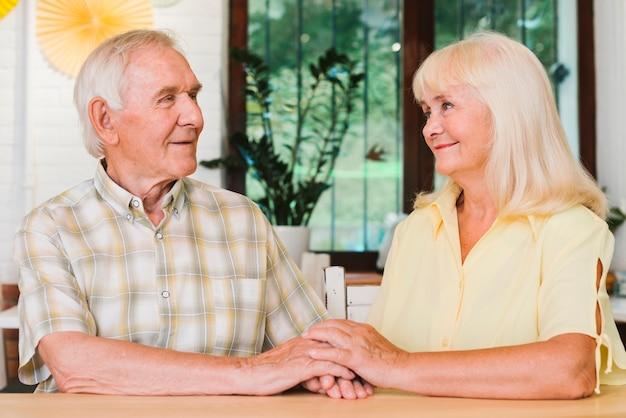 Couple de personnes âgées se tenant les mains assis