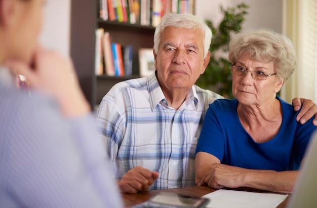 Couple de personnes âgées sérieux assis au bureau