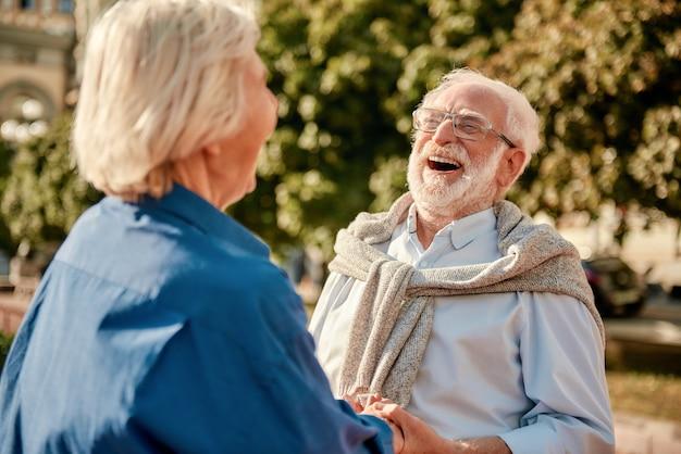 Un couple de personnes âgées si drôle, heureux et beau, se tenant la main et riant en se tenant debout à l'extérieur