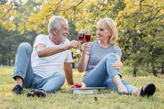 Couple de personnes âgées en sirotant du vin fruité avec un visage heureux.