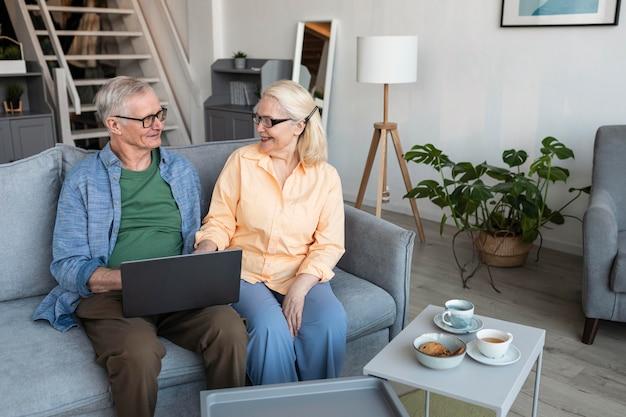 Couple de personnes âgées smiley coup moyen avec ordinateur portable