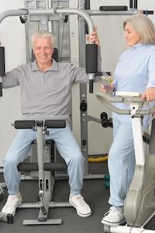Couple de personnes âgées souriant actif exerçant dans une salle de sport