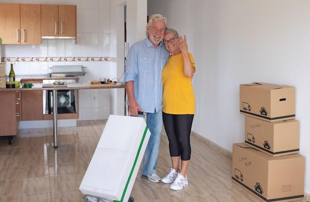 Couple de personnes âgées souriant aux cheveux blancs étreignant le signe ok dans le nouvel appartement vide avec des cartons de déménagement sur le sol - concept de personnes âgées actives et nouveau départ comme à la retraite