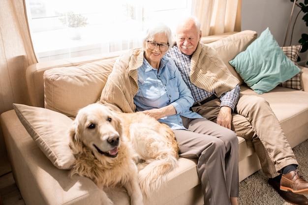 Couple de personnes âgées souriant avec chien sur canapé
