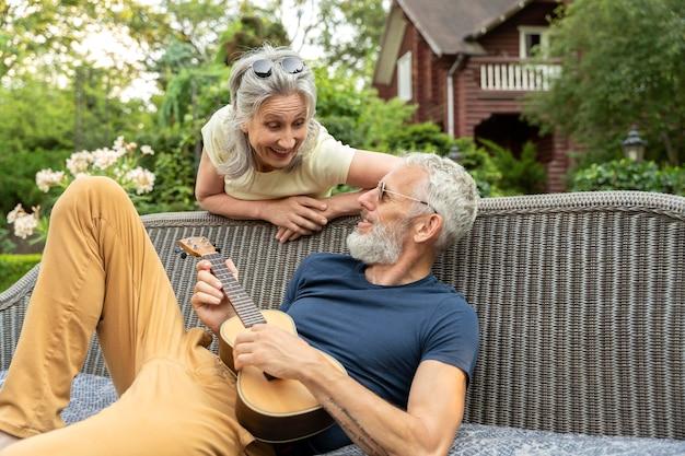 Couple de personnes âgées souriant à plan moyen avec de la musique