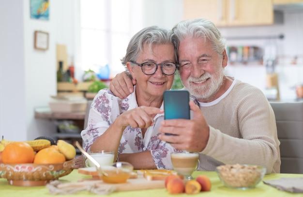 Couple de personnes âgées souriant à la recherche d'un téléphone portable pendant le petit-déjeuner à la maison