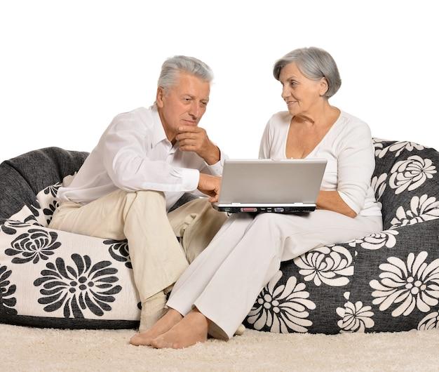 Couple de personnes âgées surpris à la recherche d'un écran d'ordinateur portable sur fond blanc