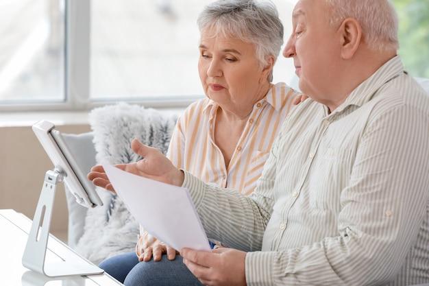 Couple de personnes âgées avec tablette à la maison